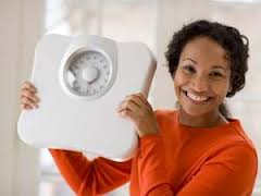 Lady who lost weight holding up a scale